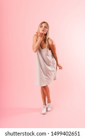 Full length image of seductive young woman wearing dress flirting and blowing air kiss at camera isolated over pink background in studio