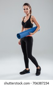 Full length image of smiling fitness woman holding fitness mat and looking at camera over gray background