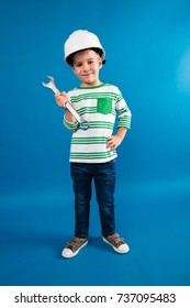 Full length image of Smiling young boy in protective helmet posing with wrench like engineer and looking at the camera over blue background