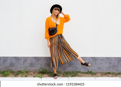 Full length image of  stylish woman  standing on white background in stylish orange sweater and multicolor stripe culotte, oversize orange knitted sweater, trendy bum bag and hat.