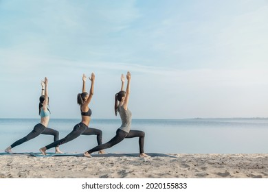 Full length image of young multiethnic group of woman practicing yoga exercise at the beach near water. Stretching exercises, active lifestyle, fitness, pilates, workout outdoors.