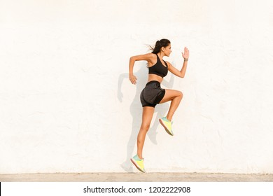 Full length image of young sportswoman 20s in sportswear working out and running along wall