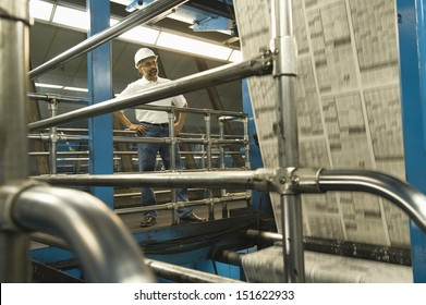 Full length of an Indian man working in newspaper factory