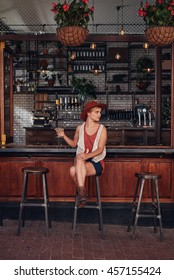 Full length indoor shot of stylish young woman relaxing at a cafe with a drink. Caucasian female sitting at a coffee shop counter and looking away.