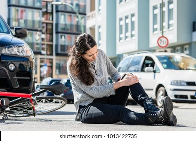 Full length of an injured young woman experiencing severe pain caused by knee sprain or fracture after bicycle accident in the city