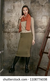 Full length isolated studio portrait of a young Asian lady in an olive skirt, a beige jacket and a terra cotta scarf. The brunette girl posing against the grunge rusty background, looking to the side.