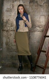 Full length isolated studio portrait of a young Asian lady in an olive skirt, a beige jacket and a navy blue scarf. The brunette girl posing over the grunge rusty background, looking at the camera.
