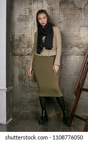Full length isolated studio portrait of a young Asian lady in an olive skirt, a beige jacket and a black scarf. The brunette girl posing against the grunge rusty background, looking at the camera.