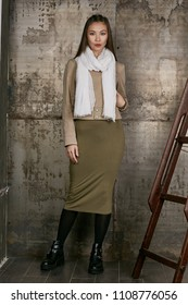 Full length isolated studio portrait of a young Asian lady in an olive skirt, a beige jacket and a white scarf. The brunette girl posing against the grunge rusty background, looking at the camera.