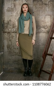 Full length isolated studio portrait of a young Asian lady in an olive skirt, a beige jacket and a sage scarf. The brunette girl posing against the grunge rusty background, looking at the camera.