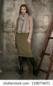 Full length isolated studio portrait of a young Asian lady in an olive skirt, a beige jacket and a grey scarf. The brunette girl posing over the grunge rusty background, looking at the camera.