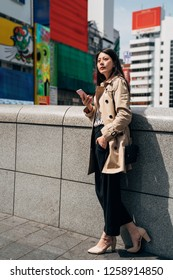 full length of japanese businesswoman texting sms message on smartphone. Happy Asian woman replying emails on mobile phone in japan. Young girl relaxing resting on the bridge enjoy sunlight.