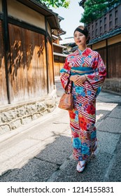 full length of Japanese lady wearing kimono and going to visit her friend in New Year.  Person in kimono dress walking on street surrounding Japanese wooden house. peaceful summer lifestyle in Japan.