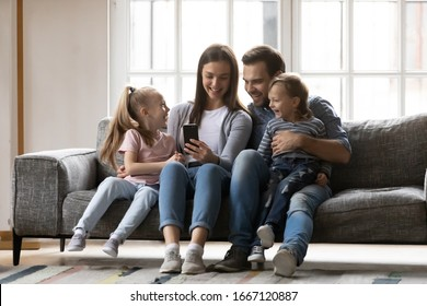 Full length joyful family of four sitting on couch, watching funny video together at home. Smiling young woman taking selfie photo with affectionate husband and cute kids son daughter on smartphone.