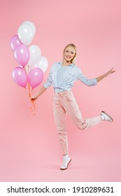 full length of joyful woman jumping and holding balloons on pink