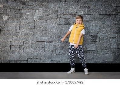 Full length of a kid having fun while doing floss dance against the wall. Copy space.