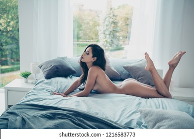Full length legs body profile side view portrait of winsome lovable fascinating lady with long hair without underwear lying on beg alone in cozy house with modern interior