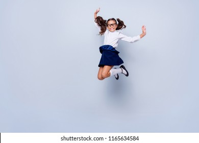 Full length, legs, body, size portrait of beautiful, pretty, charming, carefree, careless small girl in black low shoe jumping isolated on light gray background raised hand up