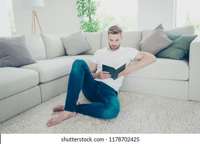 Full length, legs, body, size portrait of thoughtful man in denim outfit wear sit on the carpet floor near new couch in bright modern interior