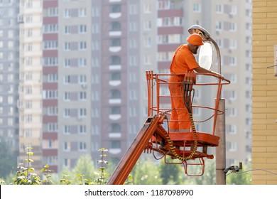Full length, legs, body, size portrait of employee workman in orange uniform, helmet raised up in bucket platform checks serviceability light lamp against on blur multi-story houses city background