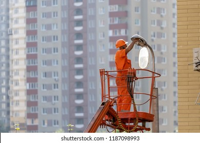 Full length, legs, body, size portrait of employee workman in orange uniform and helmet stand in staircase lift bucket changing light bulb or lamp on column against on blur city background