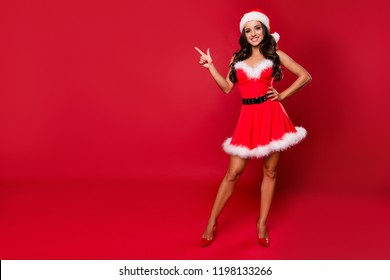 Full length, legs, body, size lady on sharp pumps stilettos with curly wave hair point show finger, forefinger on invisible product, recommend look attention on offer isolated on shine red background