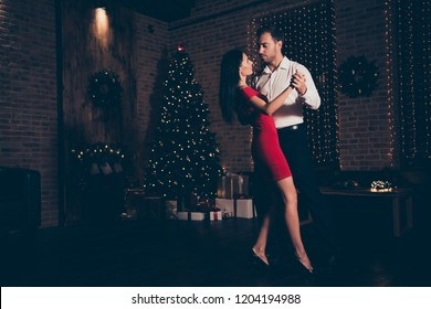 Full length, legs, body, size portrait of man in formal wear dance with lady in red dress on sharp, pumps, stilettos in darkroom with illumination garland decorations on pine tree