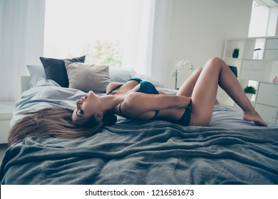 Full length legs body size portrait of beautiful nude lady in blue lace enjoying herself lying in comfort light bright room on soft bed holding her hand in panties and close eyes