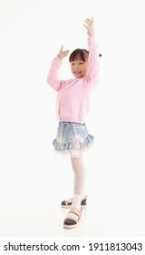 Full length of Little Asian girl standing and smiling over white background