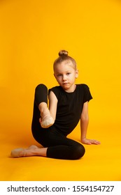 Full length little girl in black leotard stretching legs and looking away white sitting against bright yellow background during training. Little dancer in leotard stretching legs during workout