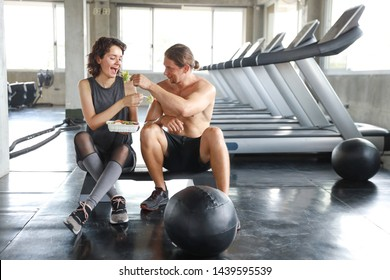full length lovely caucasian couple fitness man and woman take a rest and eating salad in gym after finish fitness training with happy smiling face