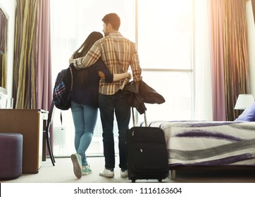 Full length of loving young couple looking through window in hotel room. Family on honeymoon