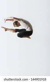 Full length of male ballet dancer jumping over white background