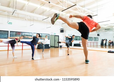 Full length of male instructor and clients kickboxing in dance class at gym