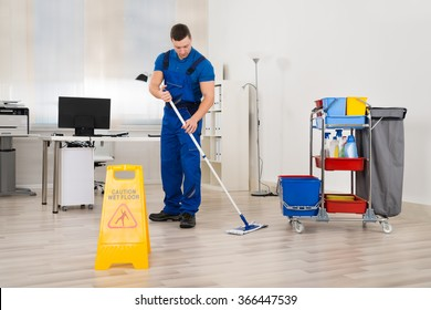 Full length of male janitor mopping floor in office