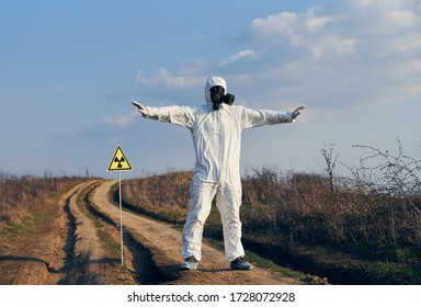 Full length of male scientist standing on the road near yellow triangle with ionizing radiation warning sign and spreading arms to sides. Research scientist wearing protective suit, gas mask.