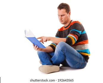 Full length male student sitting on floor reading a book preparing for exam isolated on white background
