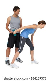 Full length of a male trainer assisting woman with dumbbell over white background