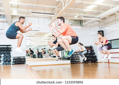 Full length of male trainer doing tuck jumps with clients in health club