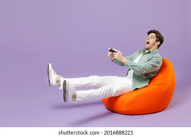 Full length man in casual mint shirt white t-shirt sitting in orange bean bag chair hold takeaway bucket eat popcorn watch movie film play pc game with joystick console isolated on purple background.