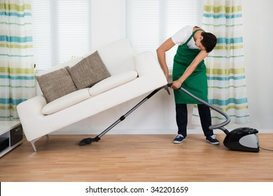 Full length of man lifting couch while cleaning hardwood floor with vacuum cleaner at home