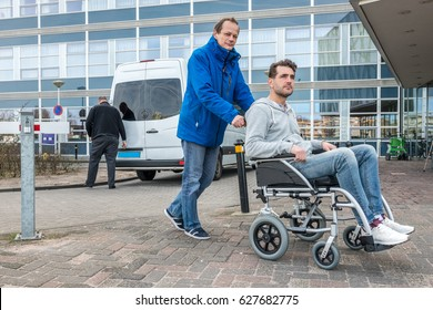 Full length of man pushing son on wheelchair with taxi driver and van in background