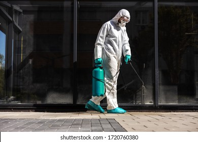 Full length of man in sterile uniform and mask sterilizing surface outdoors from corona virus, fungus and disease.