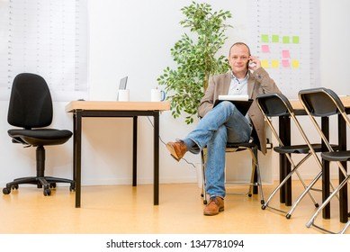 Full length of mature contractor talking on smartphone while sitting on chair in modern office