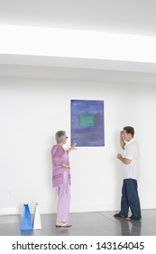Full length of mature couple discussing over painting in art gallery