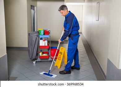 Full length of mature male worker with broom cleaning corridor