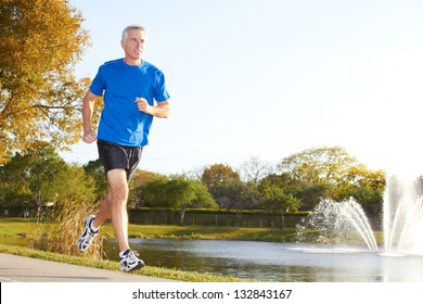 Full length of a mature man jogging with fountain in background. Horizontal shot.