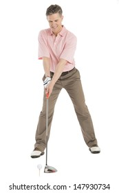 Full length of mature man playing golf against white background