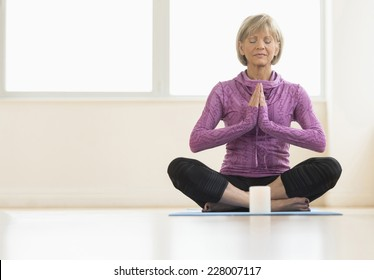 Full length of mature woman with hands clasped meditating at home