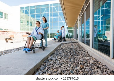 Full length of medical team with patients on wheelchairs at hospital courtyard